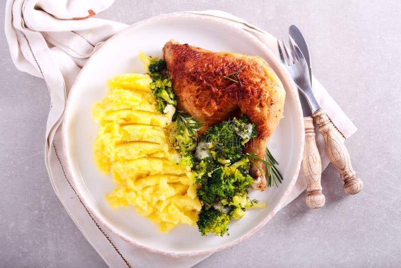 Diner - het been van de rozemarijnkip met broccoli en fijngestampte aardappel stock afbeelding