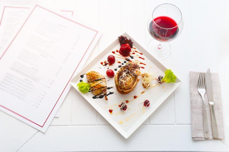 Diner of lunch met schotel per één persoon luxe wit binnenland van restaurant rode wijn en kip met peer stock fotografie