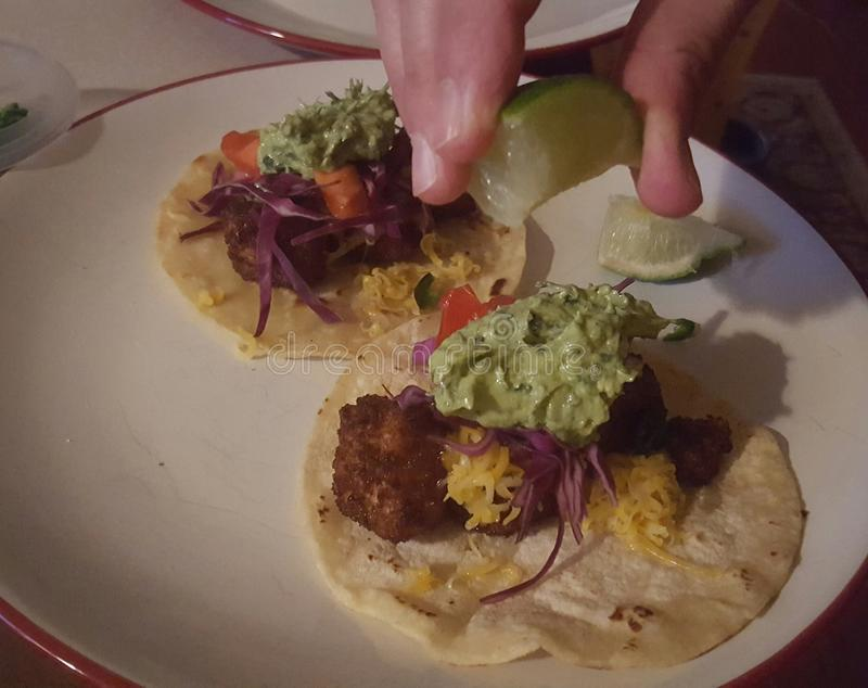 Diner squeezing lime juice onto fish tacos. Shot of fingers only, holding a piece of lime, ready to squeeze onto crispy cod fish tacos with cheese, guacamole royalty free stock image