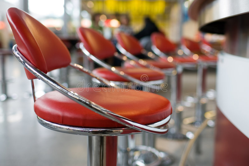 Diner stools. Line of red and chrome diner stools royalty free stock image