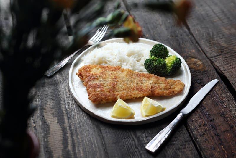 diner Vissen in broodkruimels met rijst en broccoli worden gebraden die stock foto's