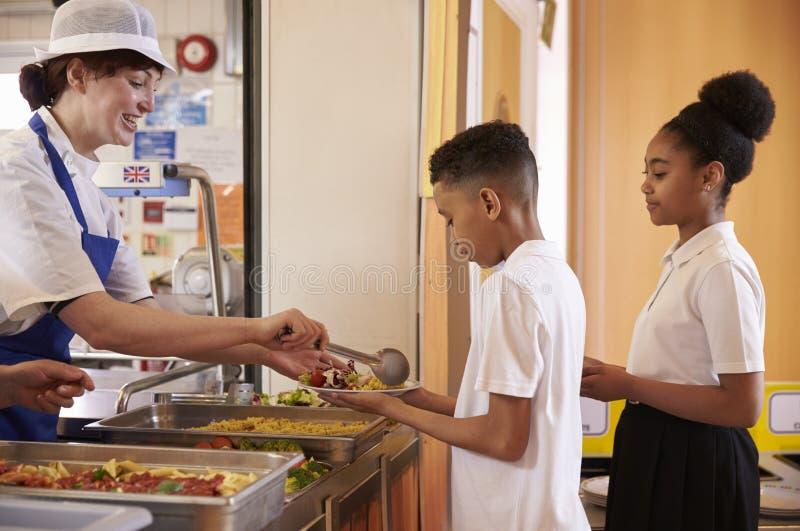 Dinerdame het dienen jonge geitjes in een schoolcafetaria, zijaanzicht royalty-vrije stock fotografie