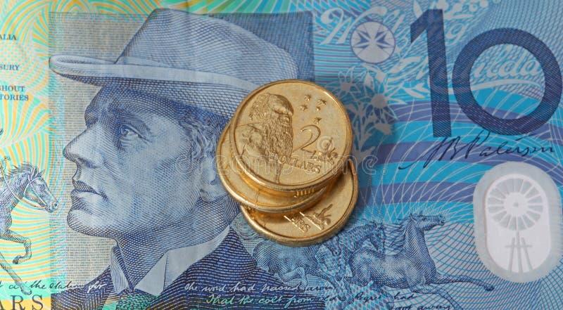 Dinero australiano billete de diez dólares y dos monedas del dólar fotos de archivo