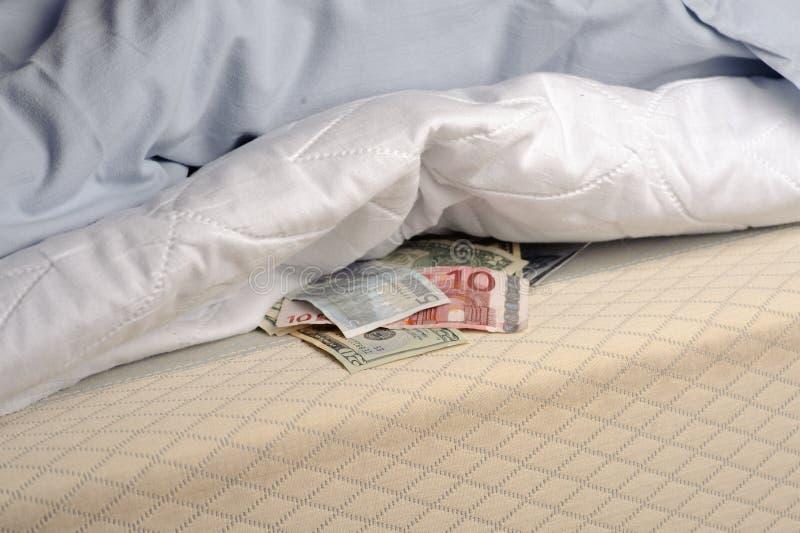 Dinero bajo el colchón imagen de archivo