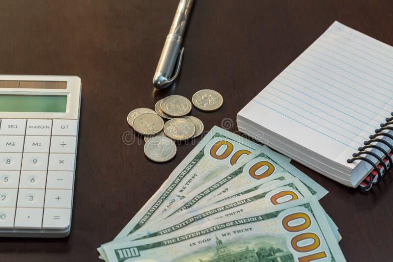Dinero, calculadora, pluma, y cuaderno en la tabla imágenes de archivo libres de regalías