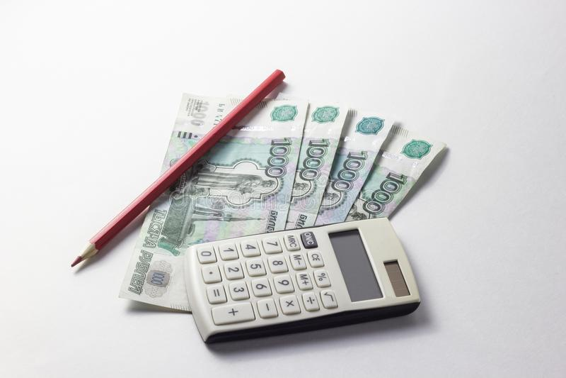 Dinero con una calculadora que miente en un fondo blanco imagen de archivo libre de regalías