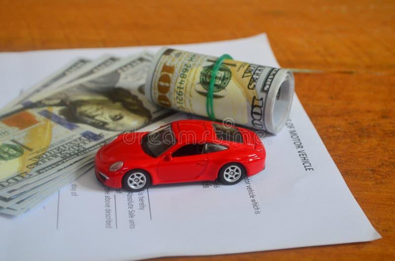Dinero, contrato de compra y un coche rojo en una tabla de madera imagen de archivo libre de regalías