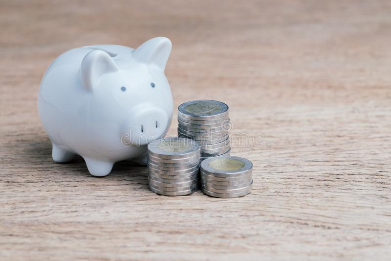 Dinero de ahorro, finanzas, presupuesto y deuda con la hucha blanca y las monedas apiladas en la tabla de madera fotos de archivo libres de regalías