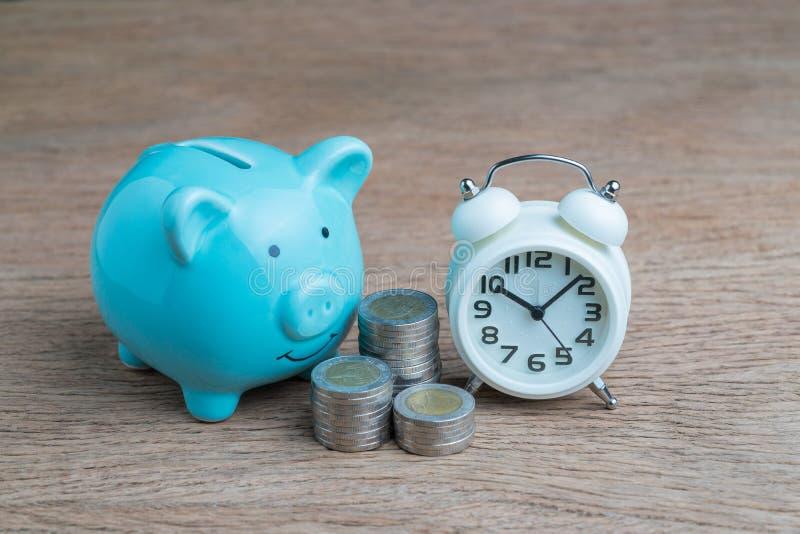 Dinero de ahorro a largo plazo financiero, concepto de control de la deuda, hucha azul, monedas apiladas y despertador en la tabl imagenes de archivo