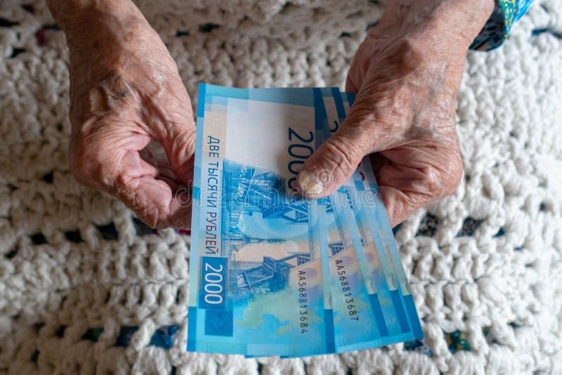 Dinero de cuenta viejo de los eyears caucásicos mayores de la mujer 90 en sus manos fotos de archivo