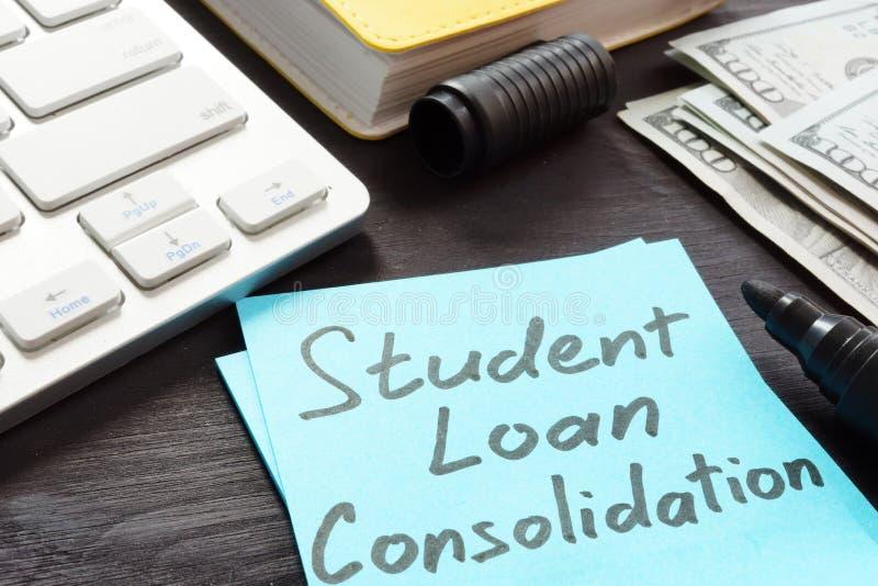 Dinero de la consolidación del préstamo del estudiante en una tabla fotos de archivo
