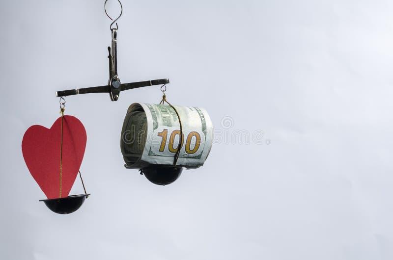 Dinero de la escala de la balanza y amar el fondo blanco Dólares y corazón imágenes de archivo libres de regalías