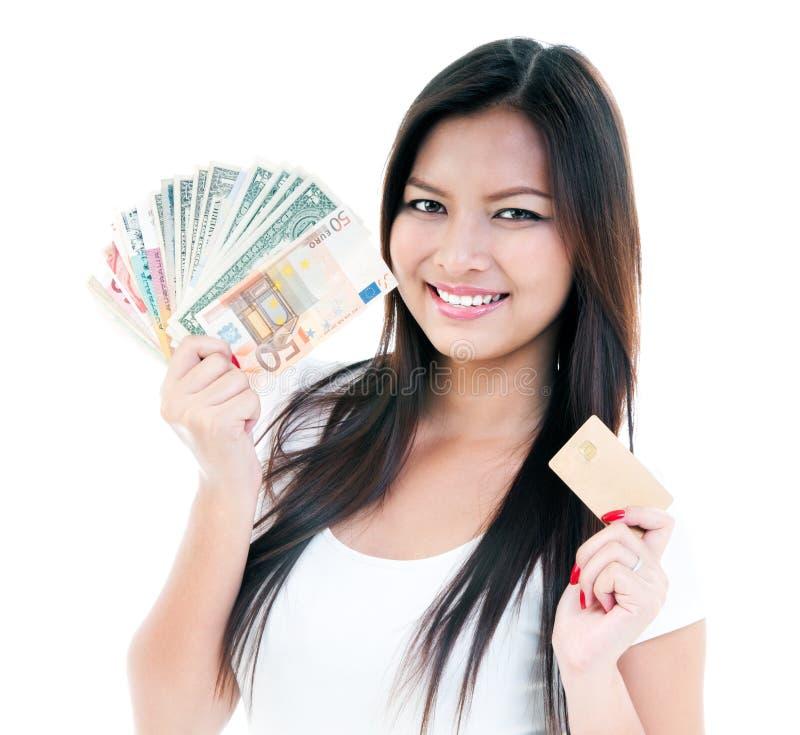 Dinero de la explotación agrícola de la mujer joven y de la tarjeta de crédito felices imagenes de archivo