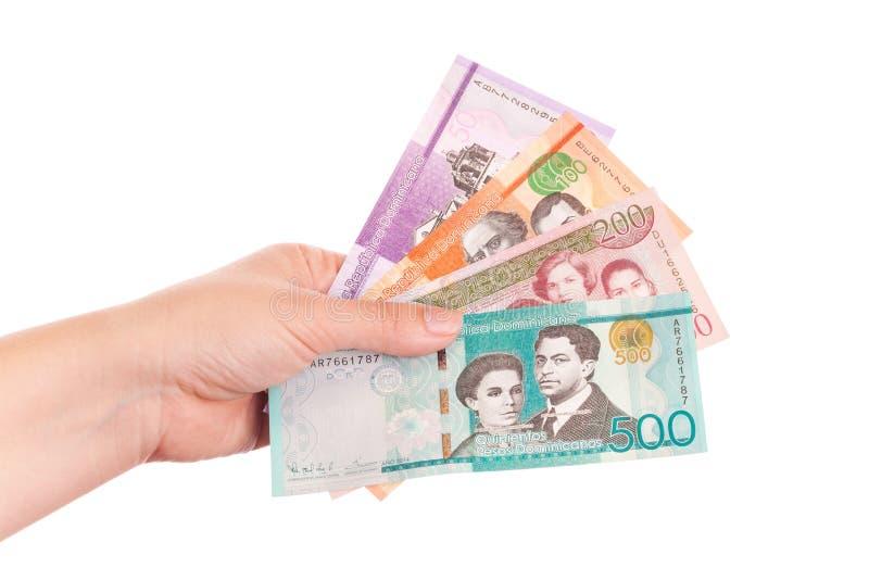 Dinero de la República Dominicana en mano femenina fotos de archivo