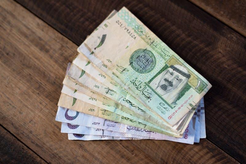 Dinero de los billetes de banco del Riyal del saudí en la tabla de madera imagen de archivo libre de regalías