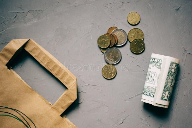 Dinero de los dólares del efectivo, monedas euro con un paquete de Kraft en gris imagen de archivo libre de regalías