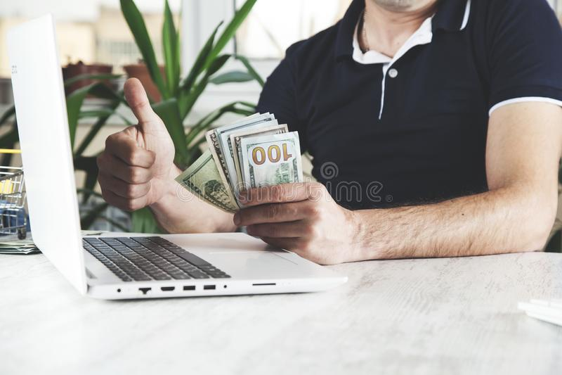 Dinero de mano del hombre con el teclado foto de archivo