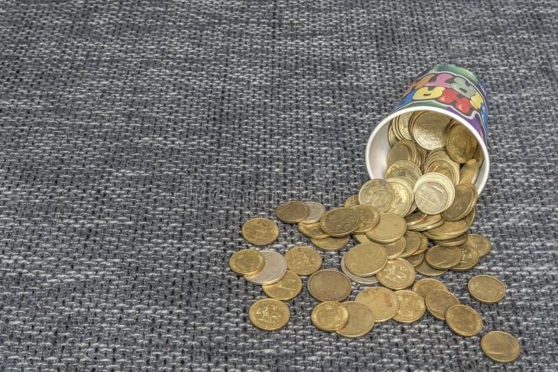 Dinero de metal derramado de un vidrio fotos de archivo libres de regalías
