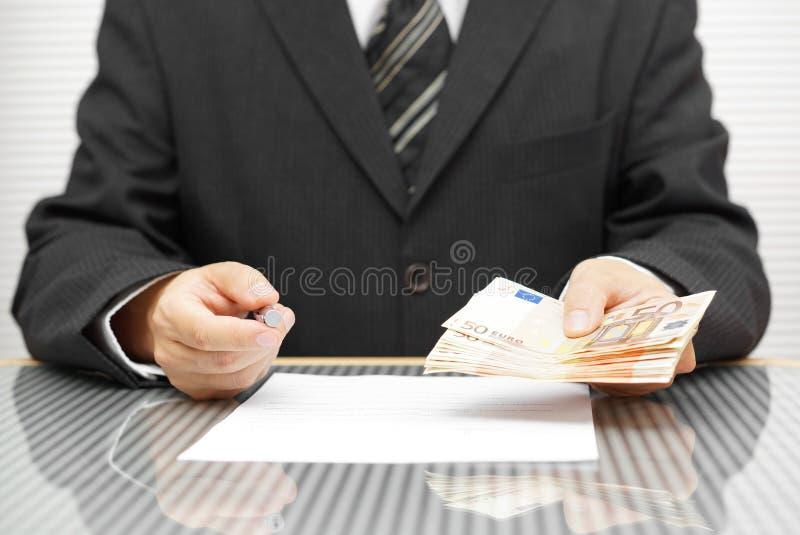 Dinero de ofrecimiento del banquero si usted firma el contrato foto de archivo