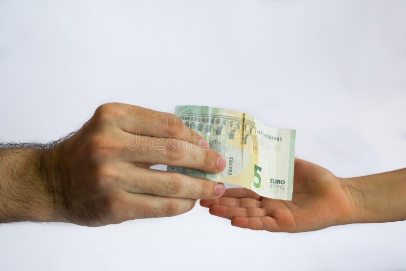 Dinero de ofrecimiento del hombre a un ni?o Dinero en manos foto de archivo libre de regalías