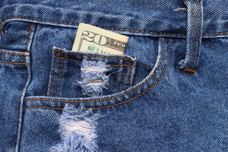 Dinero del billete de banco veinte dólares americanos en el mini bolsillo de tejanos fotografía de archivo libre de regalías