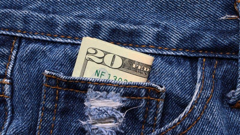 Dinero del billete de banco veinte dólares americanos en el mini bolsillo de tejanos imagen de archivo