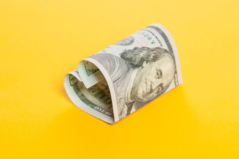 Dinero del dólar Corazón de la nota de 100 cuentas sobre fondo amarillo Interés del depósito y concepto comercial del beneficio d imagenes de archivo