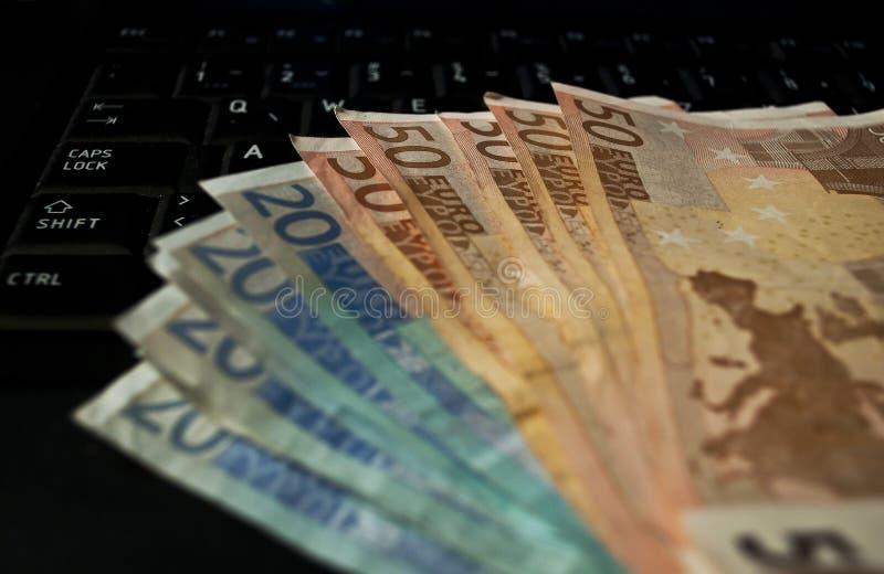 Dinero del efectivo en el teclado del ordenador portátil foto de archivo libre de regalías