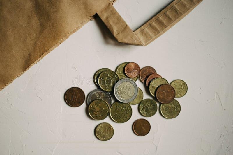 Dinero del efectivo, monedas euro con un paquete de Kraft en el fondo blanco fotografía de archivo