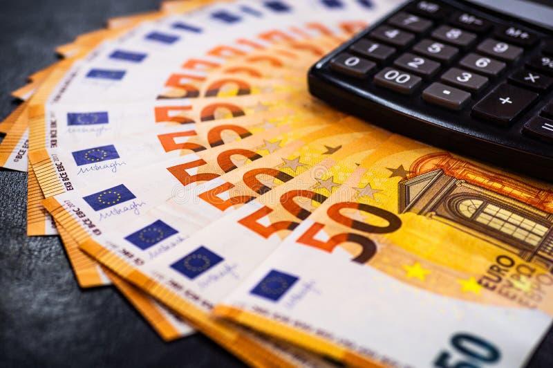 Dinero del euro 50 fondo euro del efectivo Porciones de dinero euro en la calculadora Fondo de los billetes de banco de los euros fotografía de archivo libre de regalías
