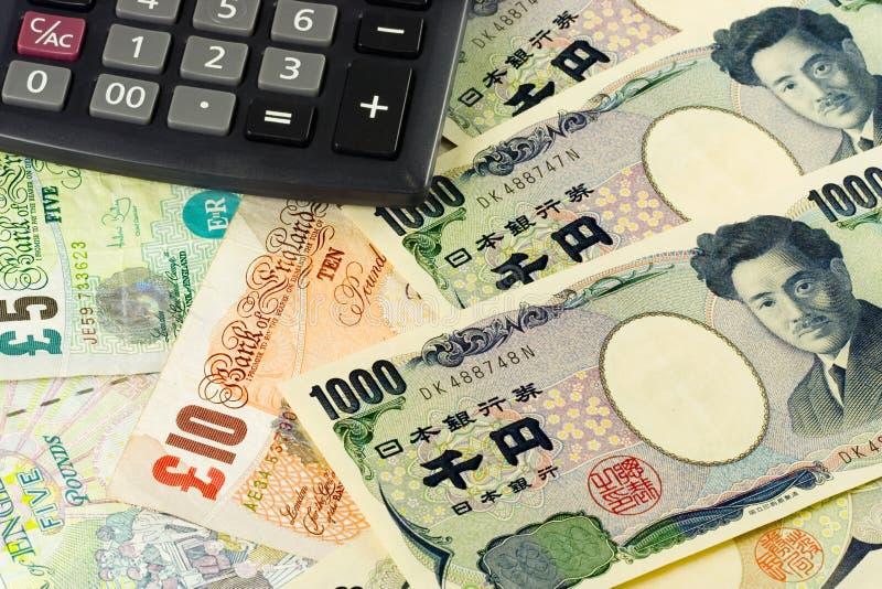 Dinero en circulación británico y japonés fotos de archivo