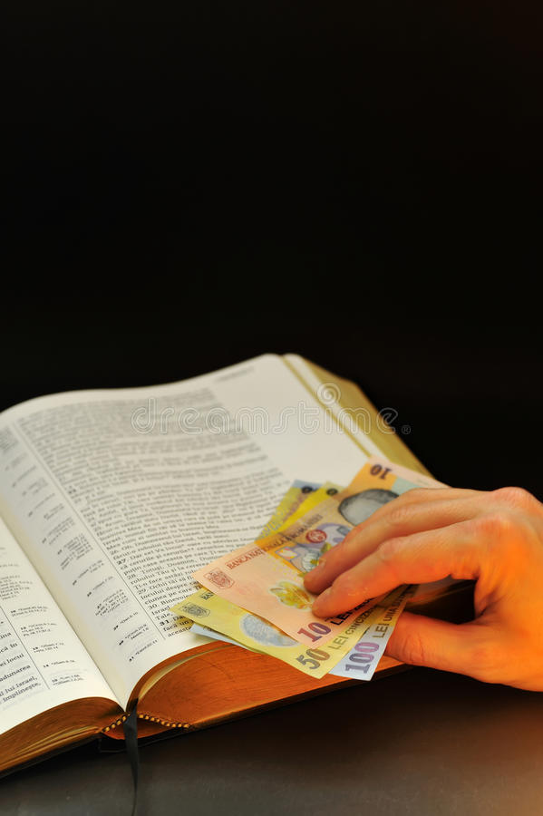 Dinero en circulación rumano de ofrecimiento y biblia santa imágenes de archivo libres de regalías