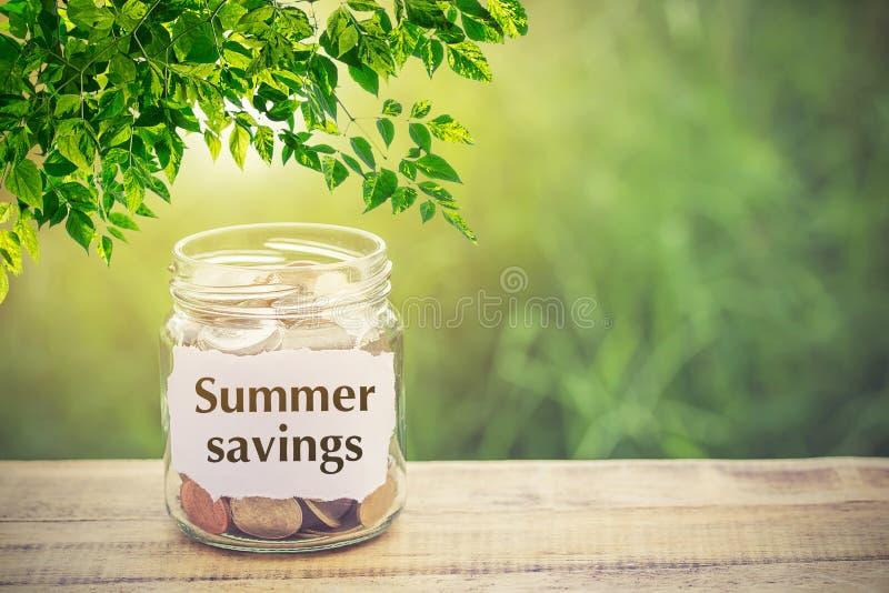 Dinero en el tarro en ahorros de madera del verano de la tabla y del texto foto de archivo libre de regalías