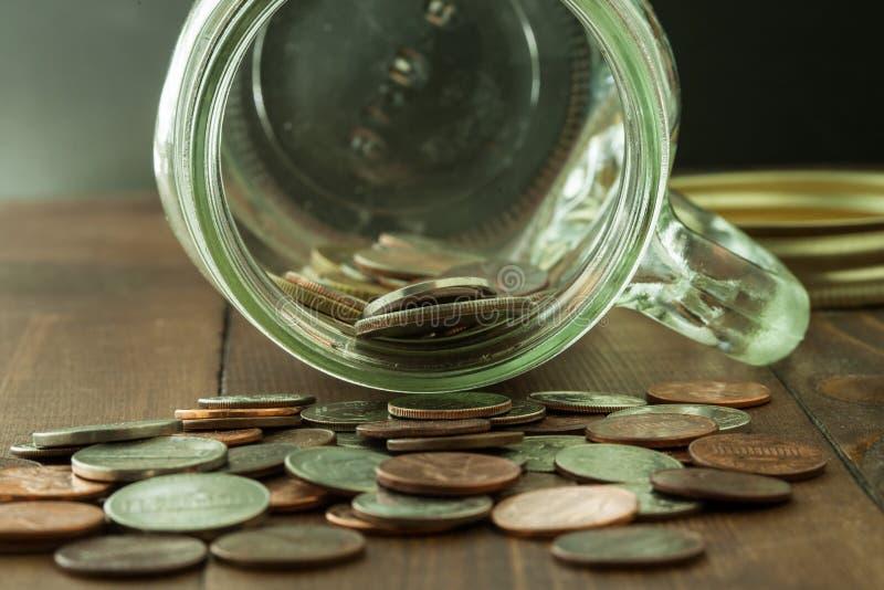 Dinero en el tarro de cristal en la tabla de madera con el focusingt selectivo fotografía de archivo libre de regalías