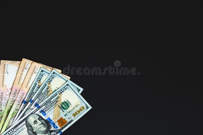 Dinero en fondo negro Fondo con el espacio para el texto dólares y hryvnia grandes de las notas imagen de archivo