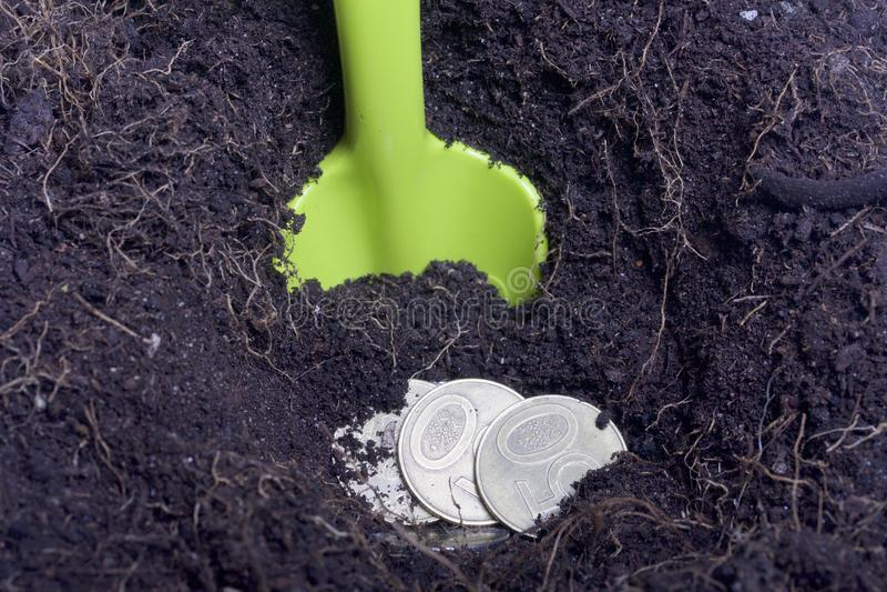 Dinero enterrado en la tierra Se excava el hoyo, las monedas está en él Una pala resalta de la tierra fotografía de archivo