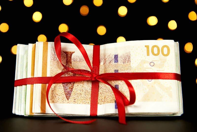 Dinero envuelto por un regalo de Navidad imágenes de archivo libres de regalías