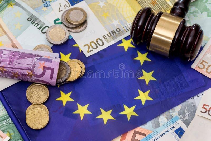 Dinero euro con el martillo en bandera del eu imagen de archivo