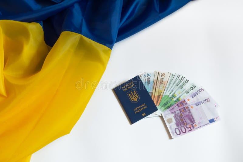 Dinero euro de la bandera ucraniana en pasaporte ucraniano fotos de archivo
