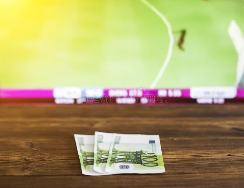 Dinero euro en el fondo de la TV en la cual hay un juego del grillo, deportes de los deportes apostando, euro imagen de archivo libre de regalías