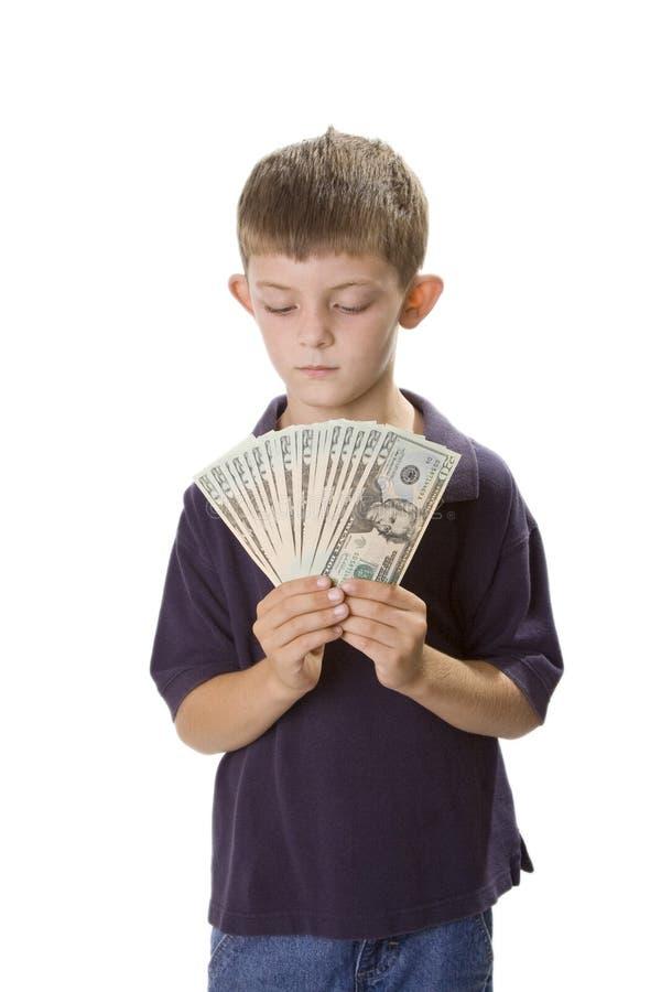 Dinero joven del efectivo de la explotación agrícola del muchacho delante de se foto de archivo libre de regalías