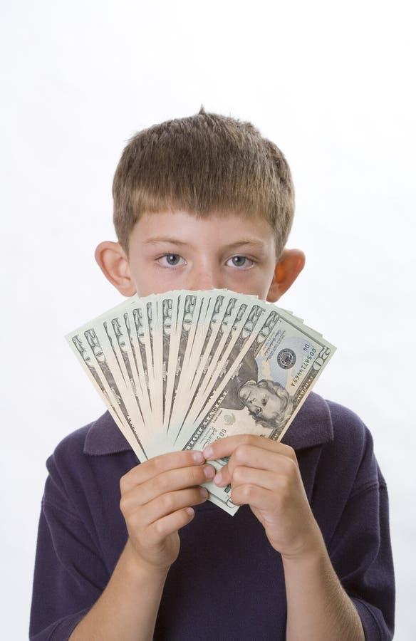 Dinero joven del efectivo de la explotación agrícola del muchacho delante de su cara imagen de archivo libre de regalías