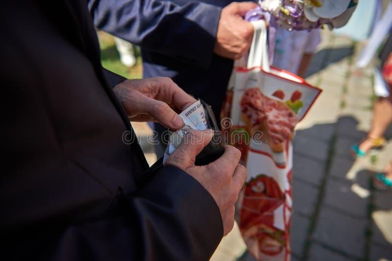 Dinero masculino de la toma de las manos del cierre de la cartera fotos de archivo libres de regalías