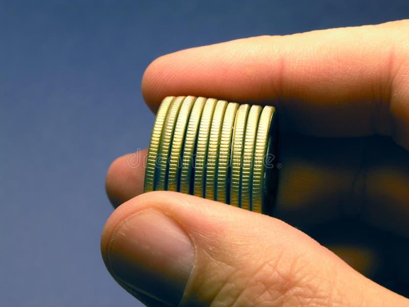 DINERO - monedas de oro sostenidas disponibles foto de archivo