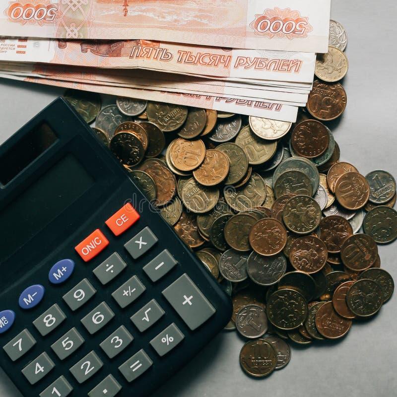 Dinero, monedas y billetes de banco rusos, calculadora en el fondo gris imagen de archivo libre de regalías