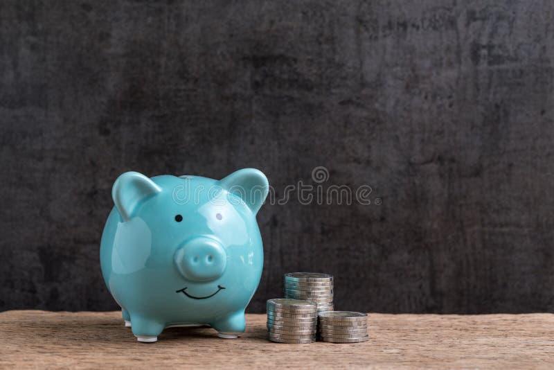 Dinero o concepto del ahorro de las finanzas, hucha azul con la pila de c imagen de archivo