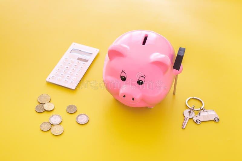 Dinero para el coche de la compra Moneybox en la forma del cerdo cerca del llavero en la forma del coche, monedas, calculadora en imagen de archivo libre de regalías