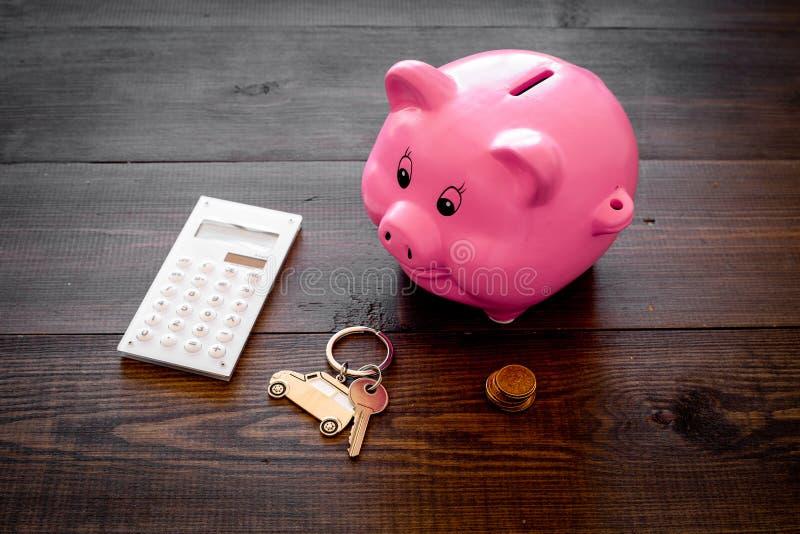 Dinero para el coche de la compra Moneybox en la forma del cerdo cerca del llavero en la forma del coche, monedas, calculadora en foto de archivo