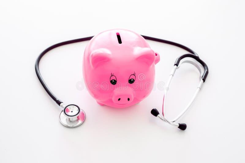 Dinero para el tratamiento Costos médicos Moneybox en la forma del cerdo cerca del estetoscopio en el fondo blanco foto de archivo libre de regalías