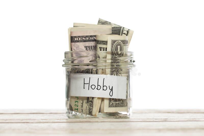 Dinero para la afición Tarro de ahorro con dólar para la afición en el tablero de madera aislado imagenes de archivo
